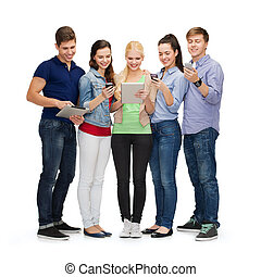 smiling students using smartphones and tablet pc - education...