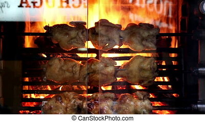 Roasted chickens on flamesover the glass window