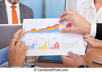 Businesspeople Analyzing Graph - Close-up Of Businesspeople...
