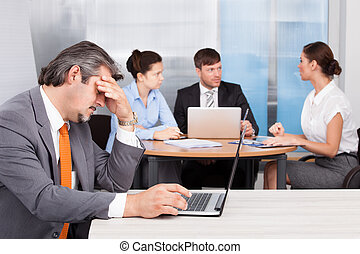 Overworked Businessman With Laptop Sitting In Front Of His...
