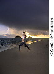 woman exercising on the beach at sunrise