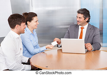 Consultant Giving Card To Couple - Mature Male Consultant...