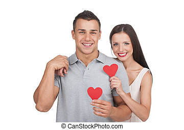 Loving couple. Beautiful young loving couple holding paper...