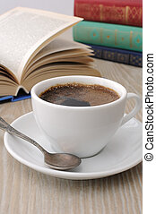 A cup of coffee on a table among books - A cup of fragrant...