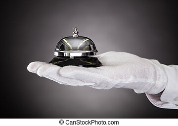 Hand Holding Service Bell - Close-up Of Hand With White...