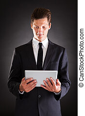 Young Businessman Using At Digital Tablet