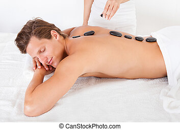 Man Getting Hot Stone Massage - Young Man Relaxing In A Spa...