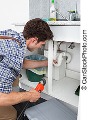 Plumber Fixing Sink In Kitchen - Young Plumber Working With...