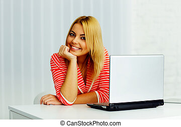 Happy young woman sitting at the table with laptop