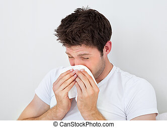 Man Sneezing Into A Tissue - Young Man Blowing His Nose In A...