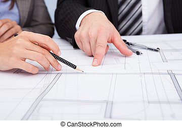 Person's Hand Pointing On Blue Print - Closeup Of A Person's...