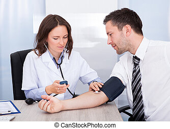 Young Doctor Checking Blood Pressure - Female Doctor...