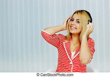 Portrait of a young woman in red jacke listening to music