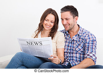 Couple Reading Newspaper - Portrait Of A Happy Young Couple...