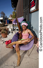 Black woman on back patio with rifle