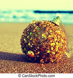 christmas on the beach - picture of a golden christmas ball...