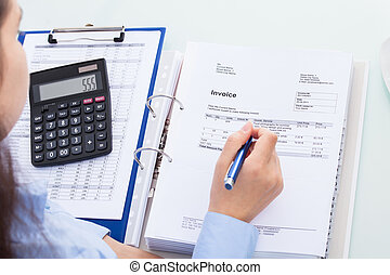 Businesswoman Calculating Invoice - Close-up Of A...