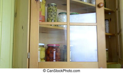 vegetable jars hand - hand opens a wooden cupboards door and...