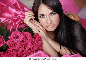 Beauty portrait of brunette girl with pink Roses lying on...
