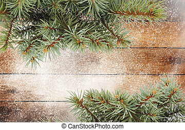 Christmas tree branch on the snow-covered wooden background