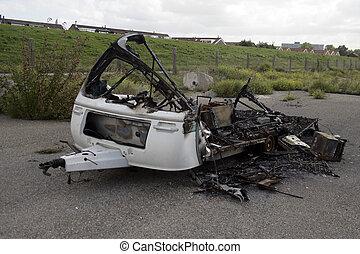 Caravan destroyed by fire - Burnt out caravan on a car park