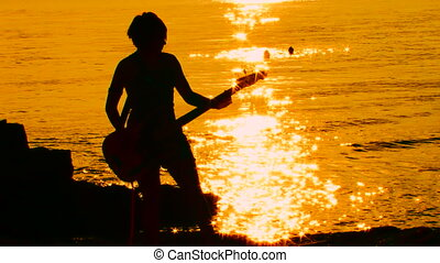 Guitarist at sunset Time lapse - Guitarist playing rock at...