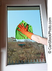 Gloved hand cleaning window with rag - hand in orange glove...