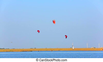 Flying kites - Kiteboarders kites flying above the sea on a...