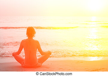 Yoga woman sitting in lotus pose on the beach during sunset, in bright colors.