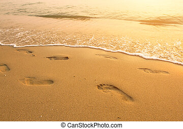 Footsteps on the beach by the sea in summer.