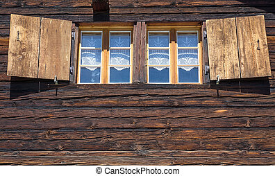 Two windows of a wooden hut seen in the swiss alps