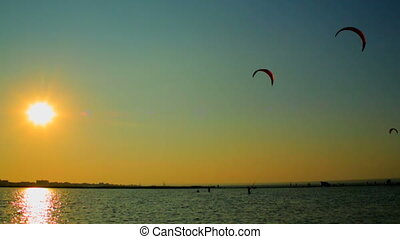 Kiteboarders at sunset - Kiteboarders surfing at sunset