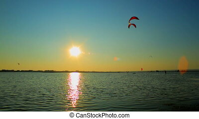 Kitesurfers at sunset - Kitesurfers surfing above the sea at...