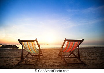 Pair of beach loungers on the deserted coast sea at sunrise,...