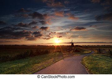 summer sunrise over Dutch windmill on farmland