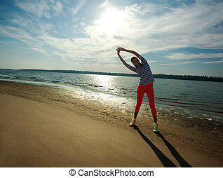 Woman exercise on the beach - Young slim woman, exercise on...
