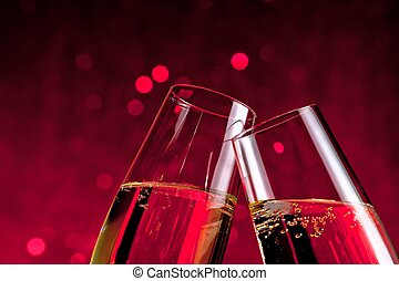 detail of champagne flutes on red light bokeh background -...