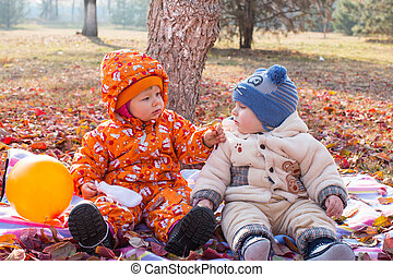 Happy child boy and girl playing with leaves in autumn park....