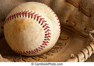 Baseball - Detail of an old baseball in a weathered glove