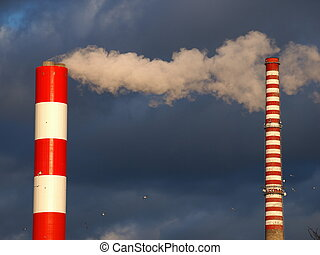 Two Chimneys illuminated on the dark clouds background