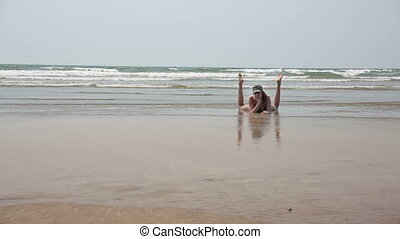 Young woman relaxing sandy beach - Young woman relaxing on...