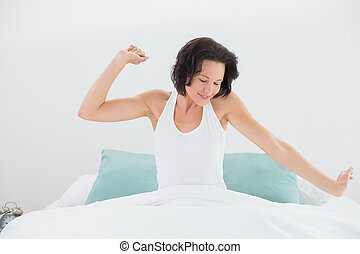 Young woman stretching arms in bed