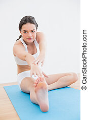 Woman doing the hamstring stretch on exercise mat