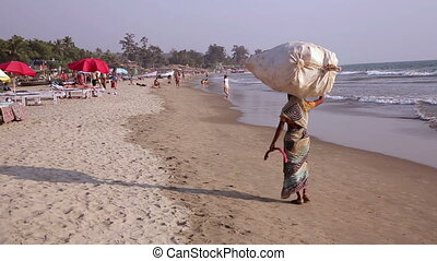 Carrying bag along sandy beach - Woman carrying bag along...