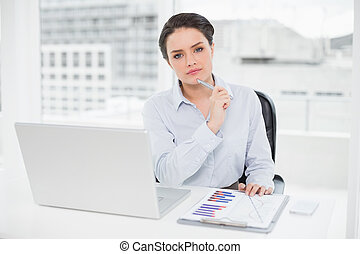 Elegant businesswoman with graphs and laptop in office -...
