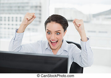 Excited businesswoman looks at the computer screen in office...