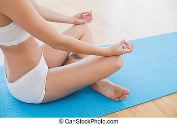 Side view of a slim cropped woman in lotus pose - Close-up...