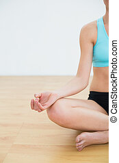 Close-up of a slim cropped woman in lotus pose at fitness...