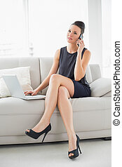 Beautiful well dressed woman using laptop and cellphone on...