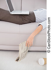 Woman with laptop and news paper lying on sofa - Mid section...